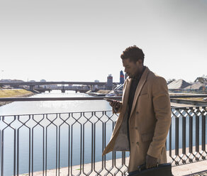 Businessman walking on a bridge with cell phone and briefcase - UUF13147