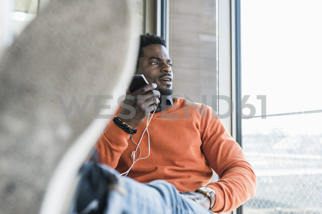 Casual businessman sitting at the window using cell phone - UUF13150