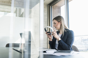 Young businesswoman with laptop and headphones working at desk in office - UUF13153
