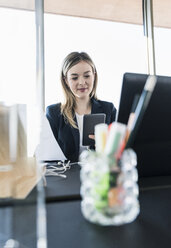 Smiling young businesswoman using cell phone at desk in office - UUF13156