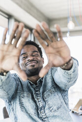 Portrait of smiling casual businessman making a finger frame - UUF13159