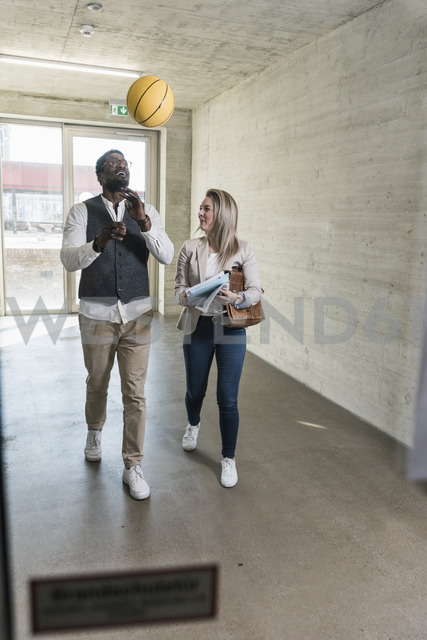 Casual businessman with basketball and busineswoman on office floor - UUF13168