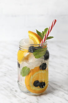 Glass of infused water with orange, blueberries and mint on ice - RTBF01100