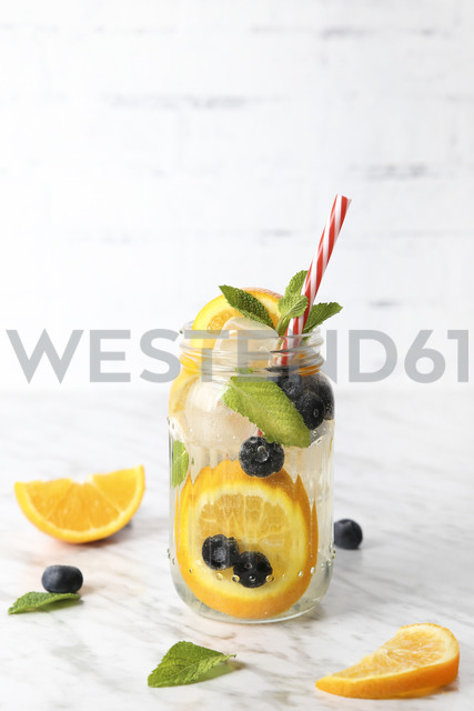 Glass of infused water with orange, blueberries and mint on ice - RTBF01103