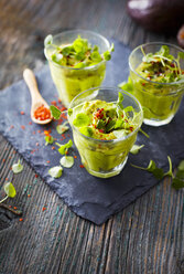 Glasses of avocado cream with chili flakes, cress and parsley - KSWF01838