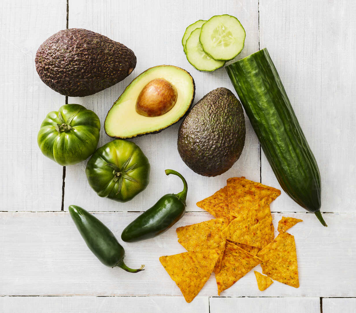 Sliced and whole avocado, green tomatoes, Jalapeno peppers, cucumber and tortilla chips - KSWF01841 - Kai Schwabe/Westend61