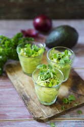 Glasses of avocado cream with chili flakes, cress and parsley - KSWF01859