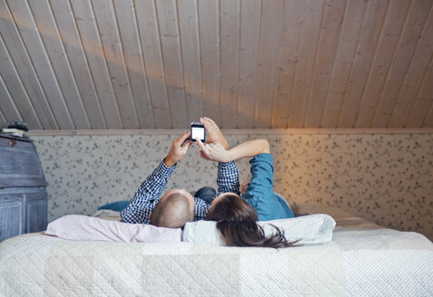 Couple lying on bed and using smart phone - FOLF00061