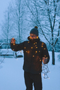 Young man holding Christmas lights at dusk - FOLF00115
