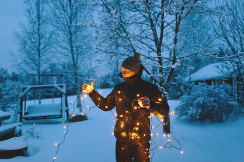 Young man holding Christmas lights in backyard at dusk - FOLF00118