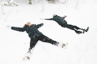 Young couple making snow angel - FOLF00124