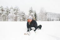 Laughing young woman sitting in snow - FOLF00127
