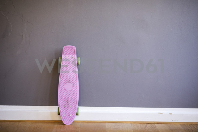Pink skateboard leaning against wall - FMKF04972