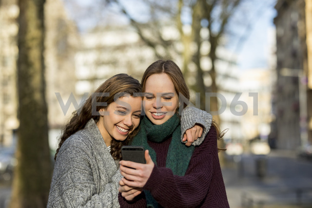 Two teenage girls taking a selfie in the city - FMKF04975