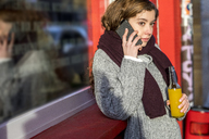 Teenage girl talking on the phone, holding bottle with a drink - FMKF04978