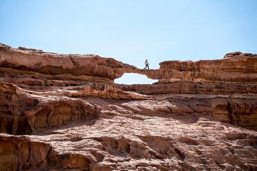 Woman walking on rock formation against clear sky - CAVF28408