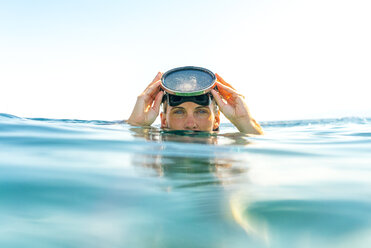 Portrait of woman swimming in sea against clear sky - CAVF28414