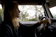 Side view of woman driving car - CAVF28417