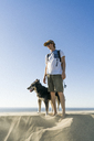 Man with dog standing at beach against clear blue sky - CAVF28432