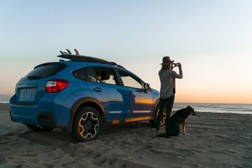 Woman photographing while standing with dog by car at beach - CAVF28438