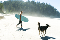 Woman holding surfboard with dog walking on sand at beach - CAVF28444