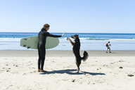 Man giving high-five to dog at beach against clear sky - CAVF28453