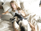 High angle view of woman with dog using laptop computer while lying on bed - CAVF28462