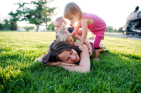 Children playing with mother lying on grassy field at park - CAVF28507