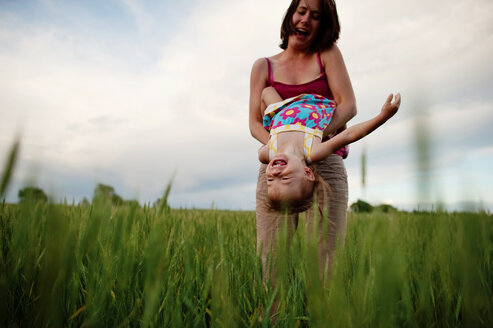 Low angle view of playful mother carrying daughter upside down on grassy field against cloudy sky - CAVF28510