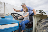 Farmer showing his daughter, how to drive a tractor - ZEF15226