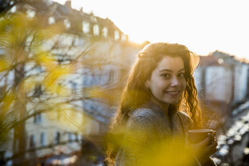 Portrait of laughing teenage girl with coffee mug on balcony at twilight - FMKF05009