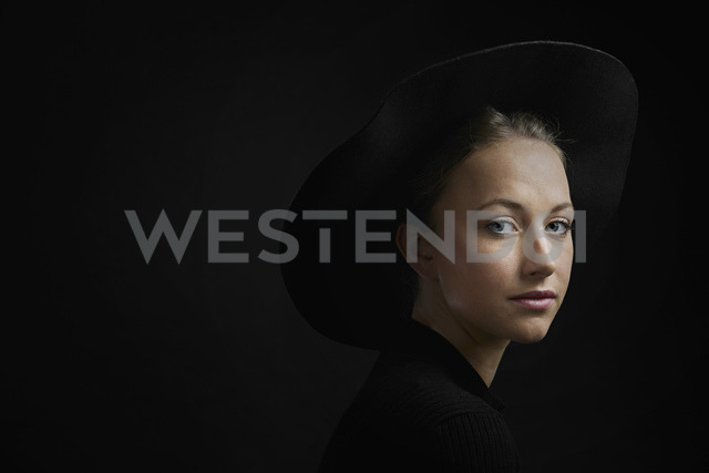 Portrait of young woman against black background - PDF01557