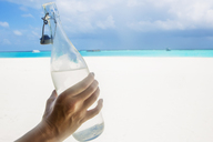 Maldives, woman's hand holding bottle of water on the beach - ZEF15244