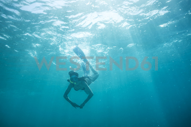 Woman with fins and snorkel diving under water - ZEF15247