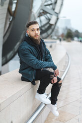 France, Paris, portrait of bearded young man sitting on a wall - AFVF00365