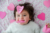 Portrait of baby girl with pink heart-shaped post it stickers - GEMF01905