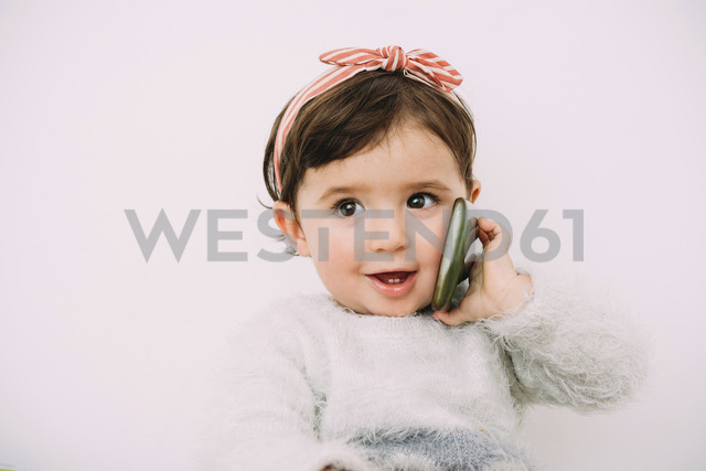 Portrait of smiling baby girl looking at cell phone - GEMF01908