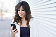 Portrait of smiling businesswoman looking at cell phone - JSMF00132