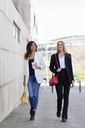 Two relaxed businesswomen with handbags and coffee to go walking on pavement - JSMF00138