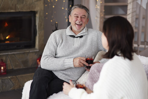 Happy mature couple with hot drinks in living room - ABIF00188