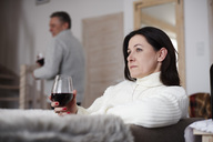 Serious mature woman with glass of wine and man in background - ABIF00191