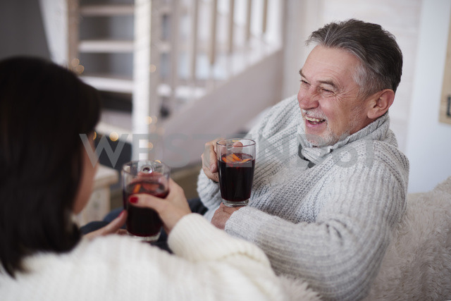 Happy mature couple with hot drinks in living room - ABIF00194