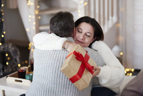 Happy mature couple with gift box hugging in living room - ABIF00197