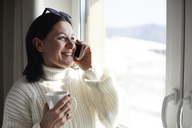 Smiling woman on cell phone at the window - ABIF00200