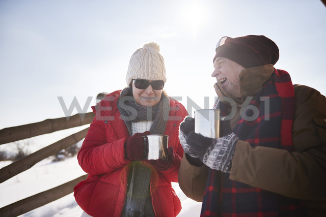Happy mature couple with hot drinks outdoors in winter - ABIF00203