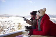 Mature couple with hot drinks talking outdoors looking at winter landscape - ABIF00206
