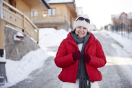 Portrait of smiling mature woman in mountain village in winter - ABIF00209