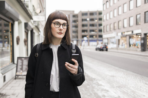 Young woman using mobile phone in street - FOLF00213
