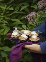 Woman holding plate with plum cakes - FOLF00366