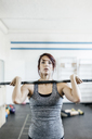 Young woman training with barbell in gym - FOLF00429